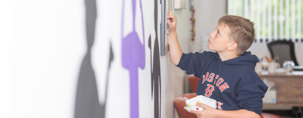 Boy at The Sycamore School painting a mural